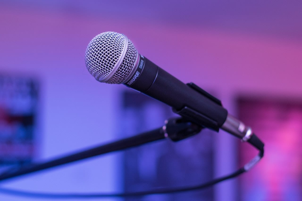 Picture of a Shure SM58 dynamic microphone in a mic stand on a purple background.