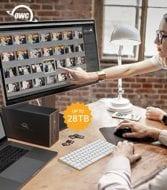 Picture of an OWC Mercury Elite Pro Dock on a desk near a MacBook Pro