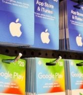 App store and iTunes gift cards and Google Play gift cards on a rack