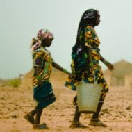 Picture of a woman and a girl carrying buckets of water in Africa.