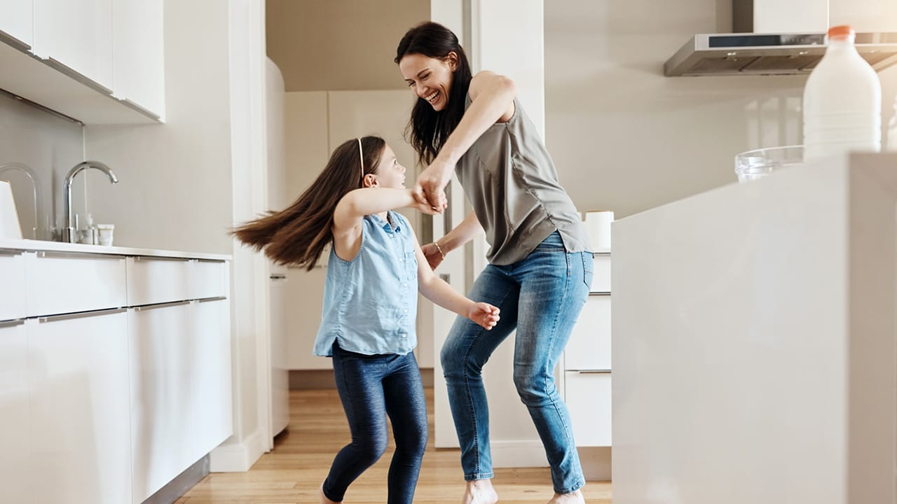 Mother and daughter dancing in kitchen