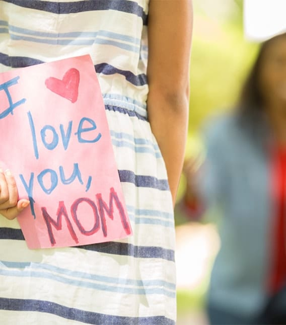 "girl holding a sign saying ""i love you mom"" behind her back"
