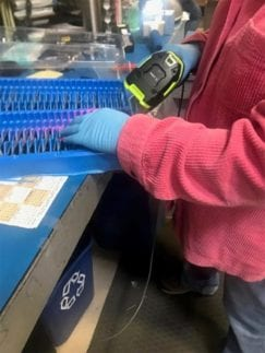 OWC employee wearing gloves and scanning product