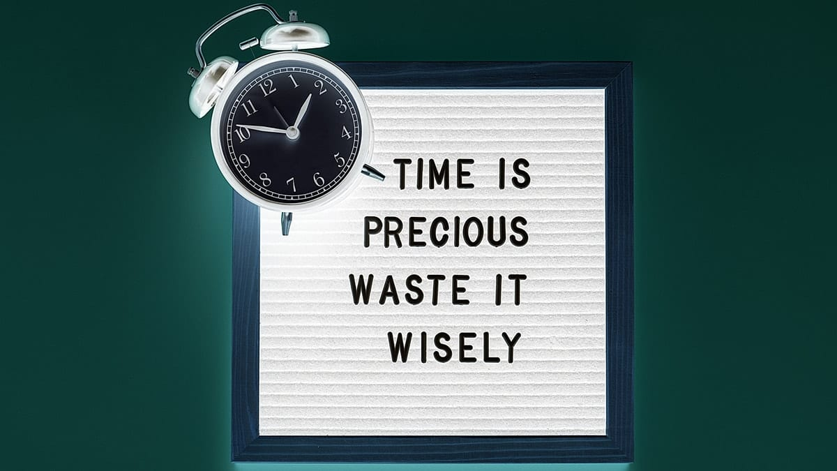 """Clock with sign saying """"time is precious waste it wisely"""""""