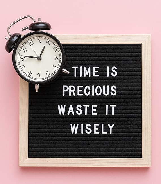 "Clock with sign saying ""time is precious waste it wisely"""