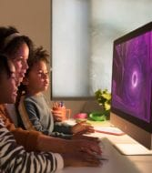 family sitting in front of an iMac with purple screen
