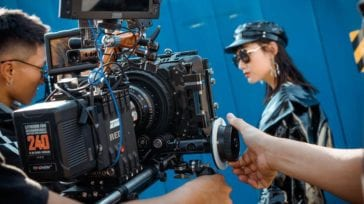 Cameraman filming a woman in leather on a blue background