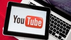 YouTube Logo on an iPad resting on a MacBook Pro
