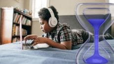 Child on a bed using a laptop overlayed with screen time logo