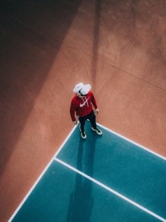 Person wearing VR headset on a tennis court