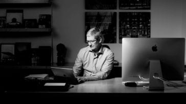Apple CEO Tim Cook sitting at a desk working on an iPad
