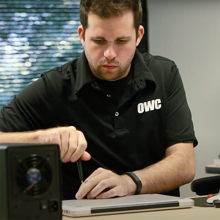 An OWC employee opening the back of a MacBook Pro