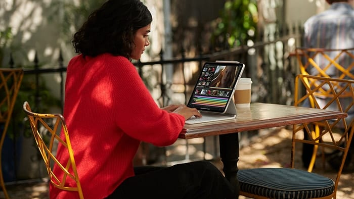 Woman sitting outside at a table editing video on an iPad